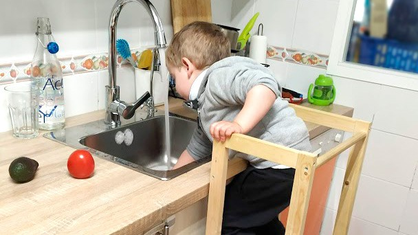 niño subido a torre de aprendizaje en la cocina